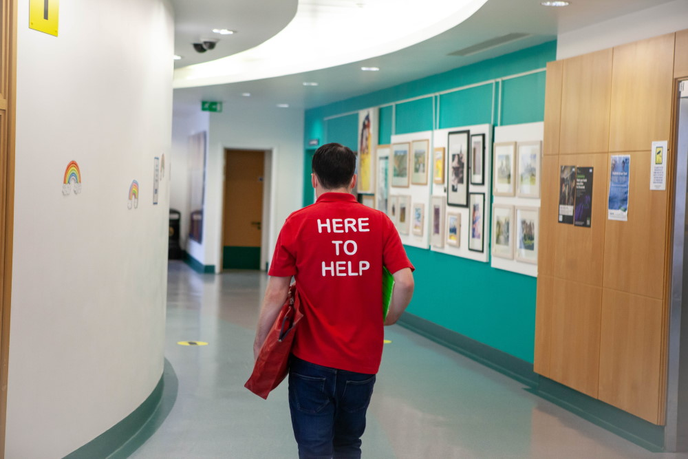 Photograph of a volunteer walking through the hospital